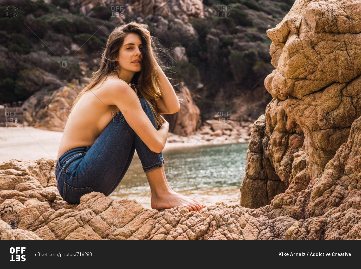 Side view of attractive topless woman sitting on rock at