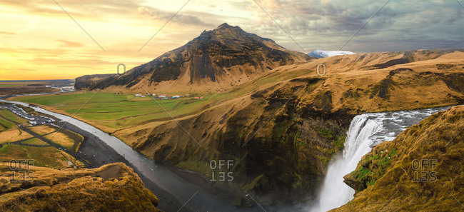 Aerial view of gorgeous landscape with texture mountains and waterfall under cloudy sky, Iceland.