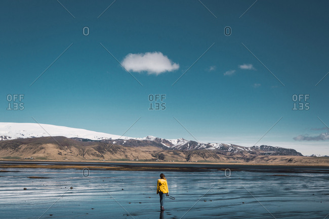 Back view of female standing near beautiful mountains with clear sky