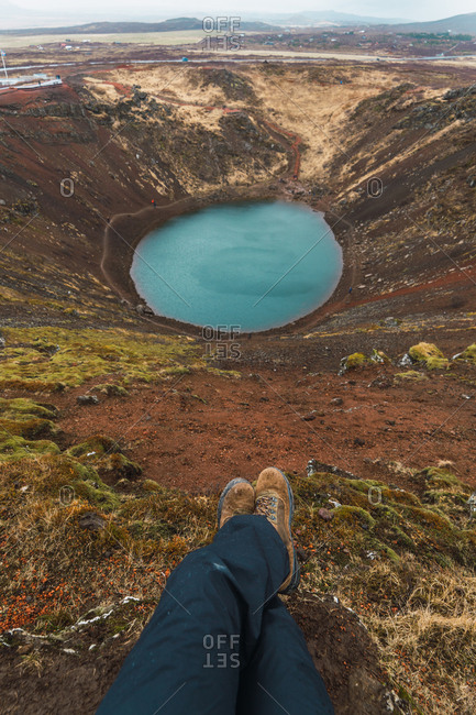 Crop shot of person with legs crossed sitting on ground with blue lake in basin below, Iceland.