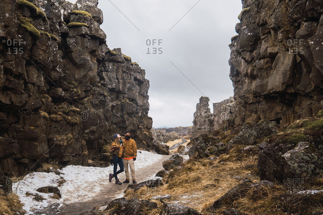 Traveling couple standing on narrow pathway among rocky cliffs with snow in gloomy day, Iceland.