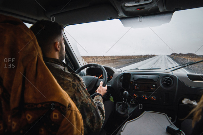 Back view of man driving car down remote road in plains of Iceland in rainy and gloomy day.