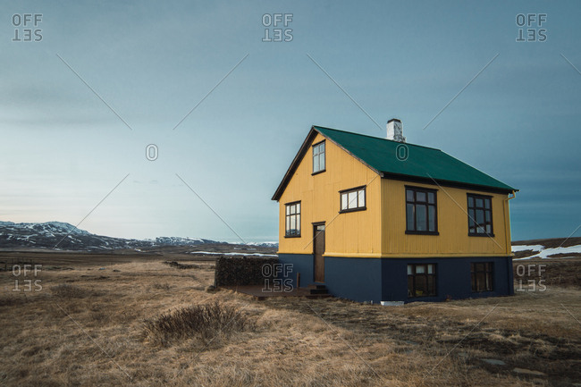 Exterior shot of colorful house placed lonely in plain of cold mountains in Iceland.