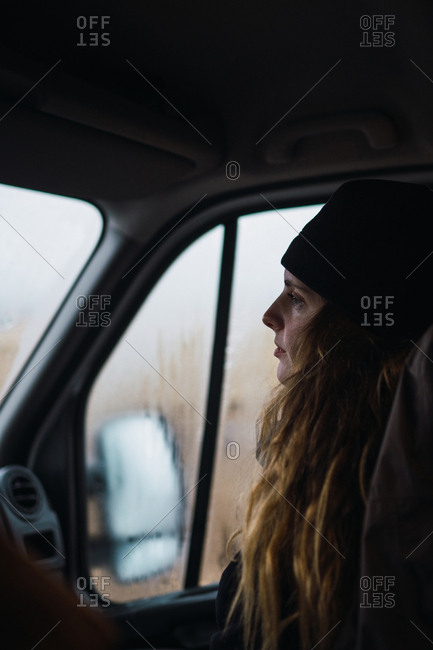 Side view of woman in hat sitting inside of car on passenger's seat looking away.