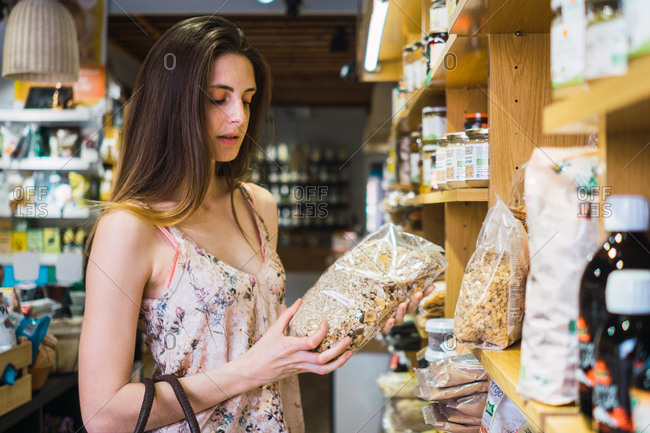 Side view of young woman choosing food for ?in supermarket