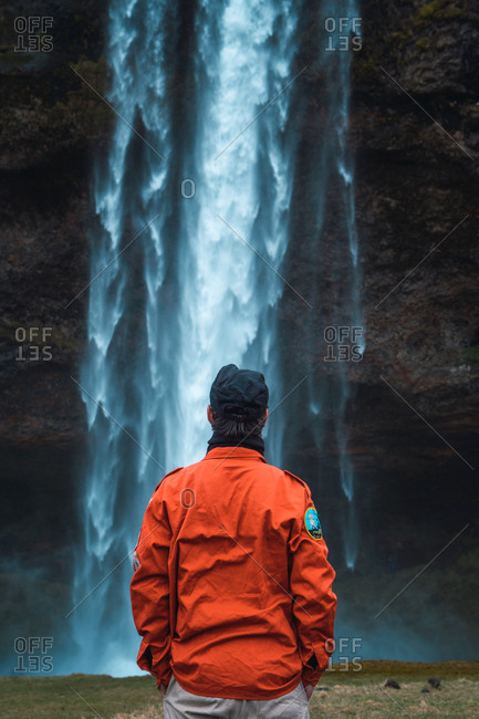 Back view of man in orange winter coat standing with hands in pockets looking at stream of waterfall, Iceland.