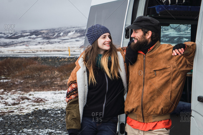 Content happy couple in outwear looking at each other standing near van in snowy valley of Iceland.
