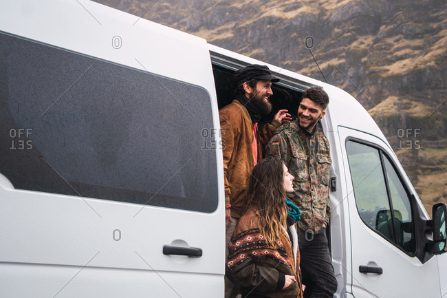 Group of cheerful men and woman in outwear standing in doors of traveling van in valley of Iceland.