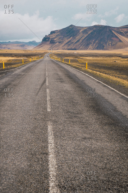 View of long paved road running far away on plain with high mountains on background, Iceland.