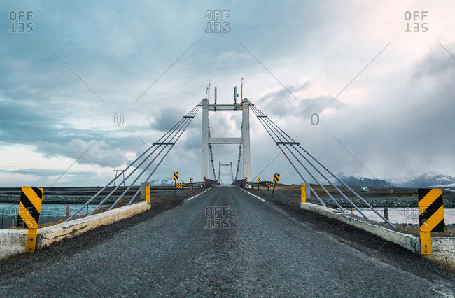 Perspective view of long paved road of suspension bridge under dark clouds, Iceland.