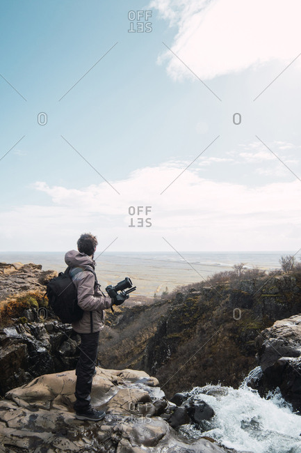 Back view of male photographer in winter clothes with backpack and camera enjoying sea view from mountain