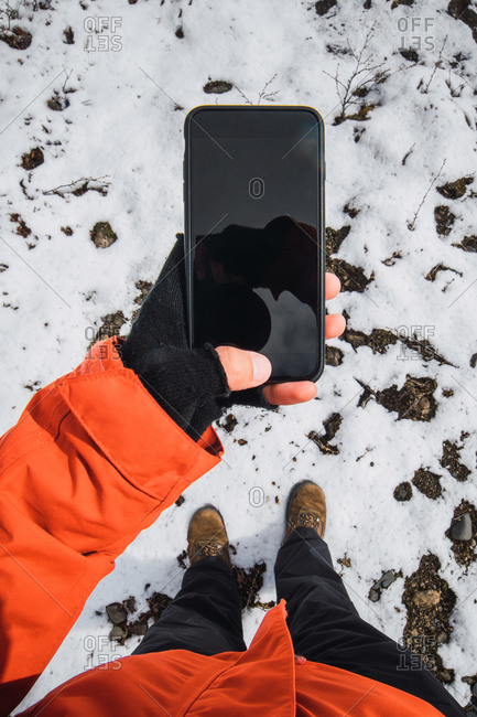 Crop view from above of person holding smartphone outside wearing winter clothes