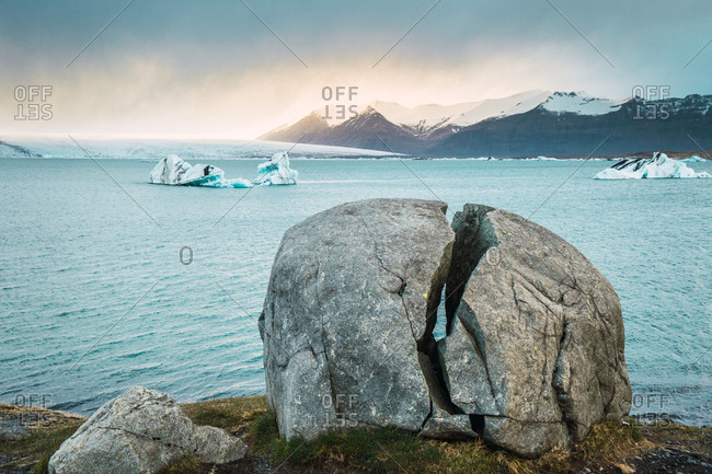 Picturesque view of split rock on cliff with background of cold ice sea of Iceland.