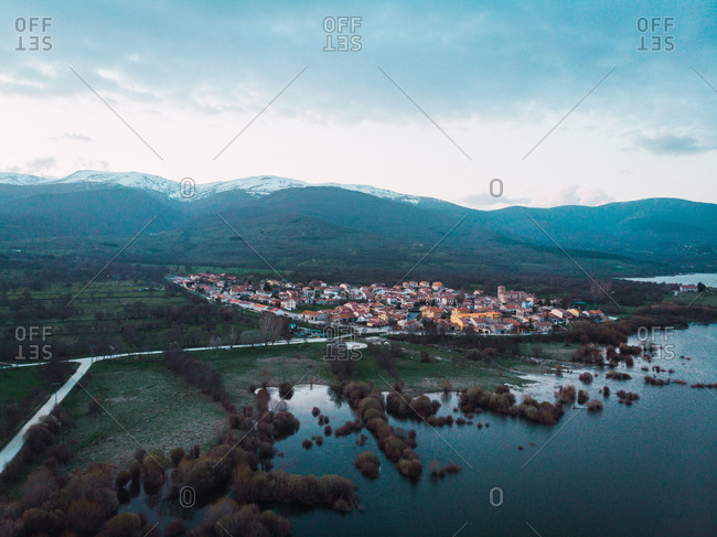 Beautiful landscape of light sky mountains with snow dark water and village with orange roofs