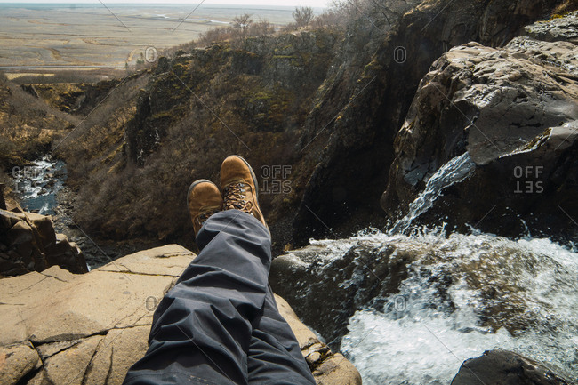 Crop legs of male sitting on top of mountain near waterfall in winter clothes