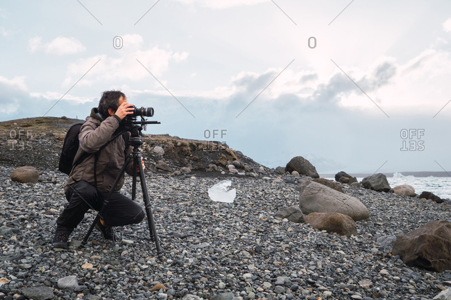 Man setting photographic equipment on coast
