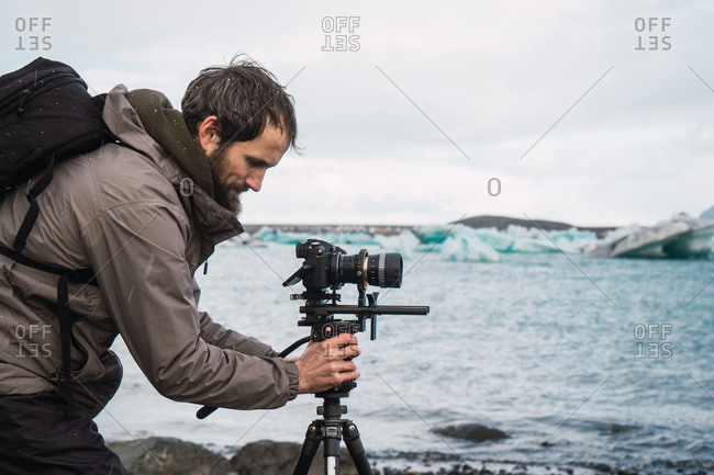 Side view of man in outwear with backpack setting photo camera on tripod to take photo of beautiful cold seascape.