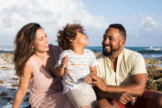 Happily smiling ethnic parents and little son sitting on sandy coast at the ocean in sunny day