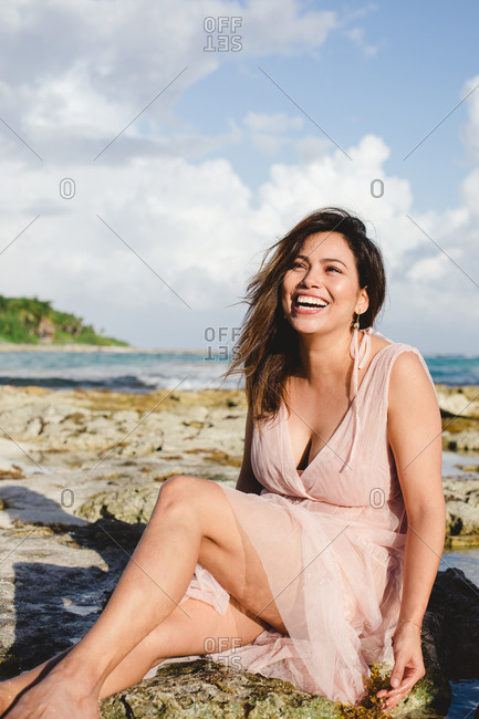 Laughing adult attractive woman sitting on sandy beach and looking away at the ocean in sunny day