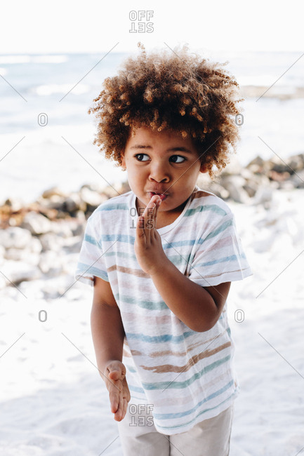 Adorable little boy playing on sand and looking away on beach at the ocean in sunny day