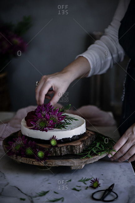 Crop woman decorating cake with flowers