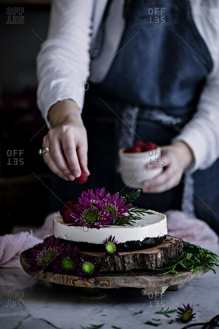 Crop woman decorating cake with berries