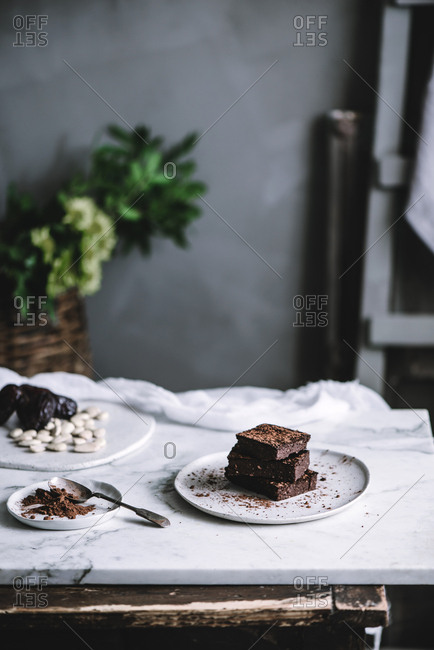 Tasty sweet vegan brownie dessert and cocoa powder on plate on a table.