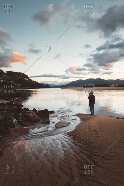 Person on tranquil beach in sunset