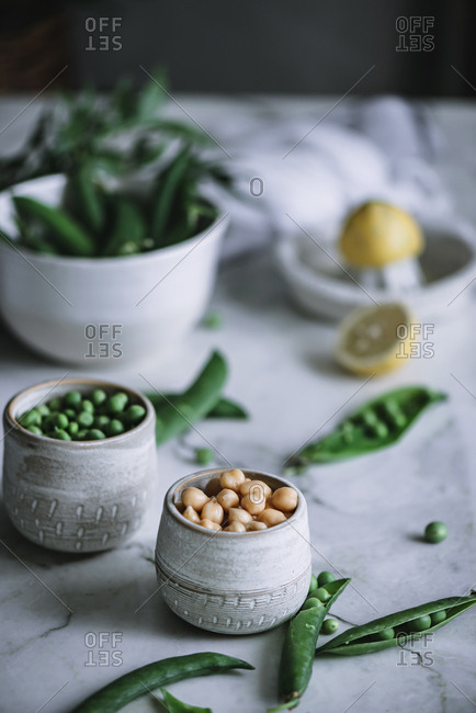 Close-up shot of small jars full of ripe peas standing on white marble tabletop