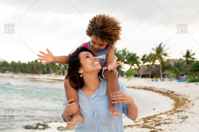 Cheerful woman with son on shoulders on beach