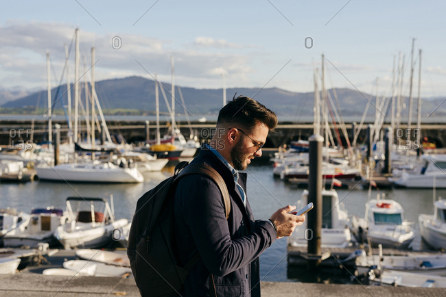 Stylish dreaming man on pier with smartphone