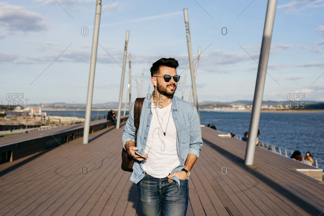 Trendy hipster strolling on waterfront