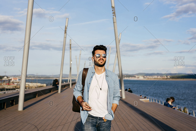 Stylish hipster man in sunglasses and with backpack listening to music and walking on wooden pier in sunlight.
