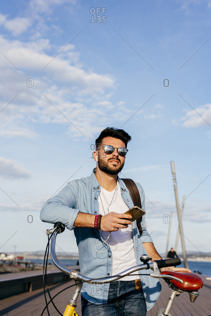 Smiling guy with bicycle and smartphone