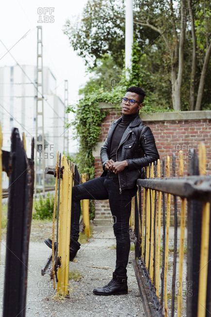 Handsome black male in leather jacket holding glasses standing near the fence
