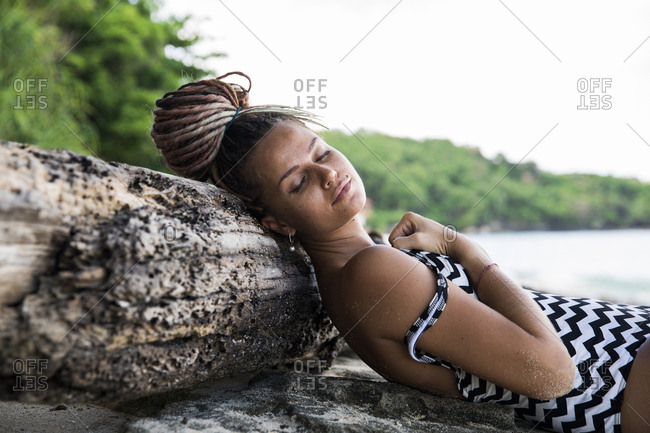 Dreamy woman in swimsuit lying on roots