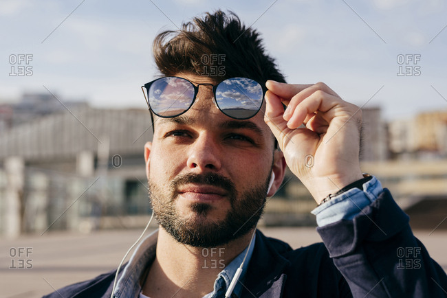 Head shot of trendy bearded man with hairstyle using headphones and taking sunglasses off looking away in sunlight.