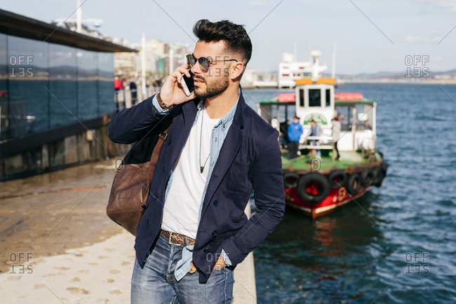 Stylish handsome man in denim and jacket having phone call while standing with leather backpack on seafront.