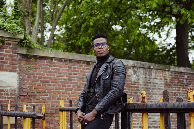 Handsome black male in leather jacket standing near the fence