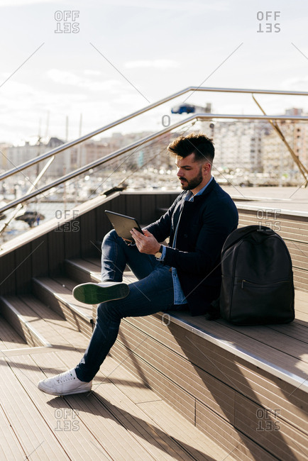 Handsome man in jacket and sneakers sitting with backpack on wooden seafront and browsing tablet in sunlight.
