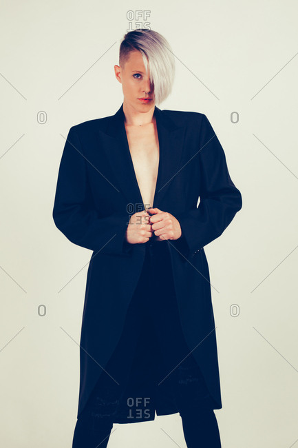 Portrait of a young woman with dark tailcoat and without shirt, shot in studio
