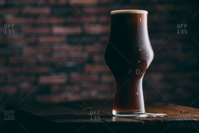 Stout beer in glass on dark background