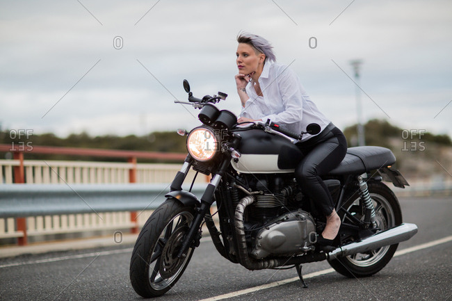Attractive young woman sitting on her cafe racer motorbike