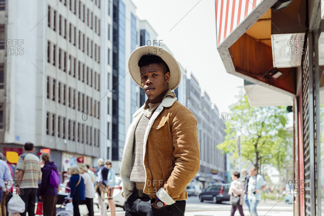 Young african male in hat and backpack looking on road with cars in metropolis