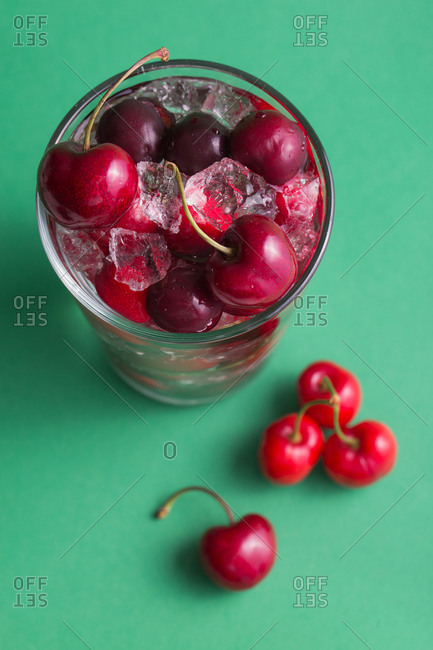 Cherries in a glass with ice on green background