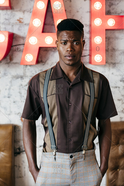 Handsome african male in pants with suspenders and shirt putting hands in pockets standing and looking at camera