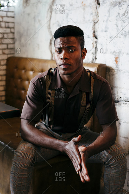 Young black man in pants with suspenders and shirt sitting on couch and looking at camera