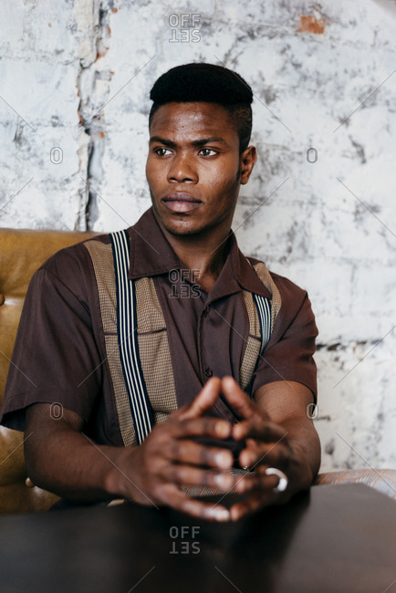 Young african male in shirt with suspenders putting hands with ring on table