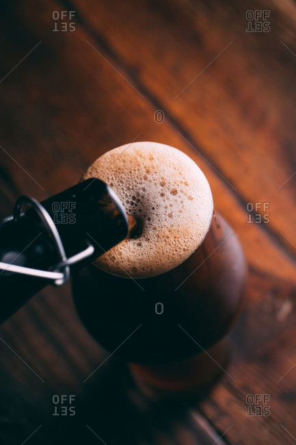 Serving stout beer in glass on dark background