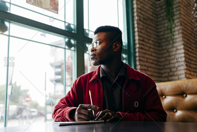 Serious african male in red jacket letter at table in cafe